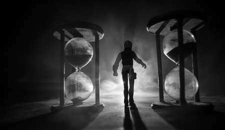 Time concept. Silhouette of a man standing between hourglasses with smoke and lights on a dark background. Surreal decorated picture