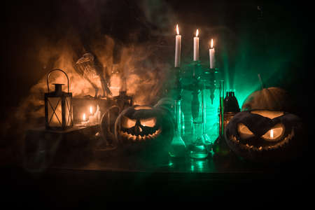 Wizard's Desk. Horror Halloween concept. Magic potions in bottles on wooden table with books and candles. Halloween still-life background with different elements on dark toned foggy background. Selective focus Imagens
