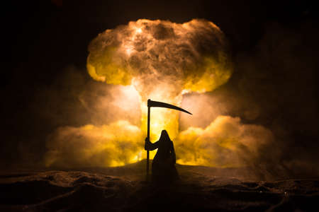 Nuclear war concept. Explosion of nuclear bomb. Creative artwork decoration in dark. Silhouette of grim reaper looking on giant mushroom cloud of atomic explosion. Selective focus Banque d'images