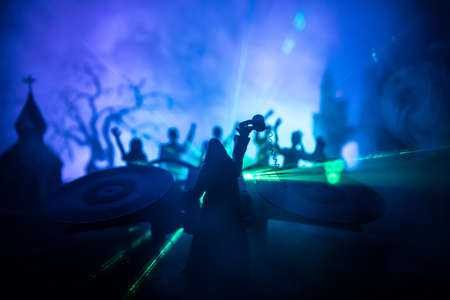 Happy Halloween horror party concept. Scary view of dancing zombies at cemetery with Dj and club lights. Creative artwork decoration. Useful as a party poster or greeting card. Selective focus