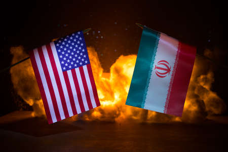 USA and Iran small flags on burning dark background. Concept of crisis of war and political conflicts between nations. Selective focus