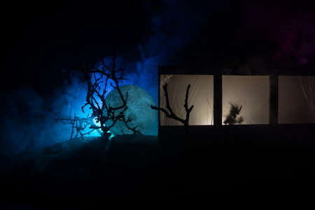 Artwork decoration. Old house with a big windows and zombies inside. Blurred scary silhouettes at window. Horror halloween concept Stock Photo