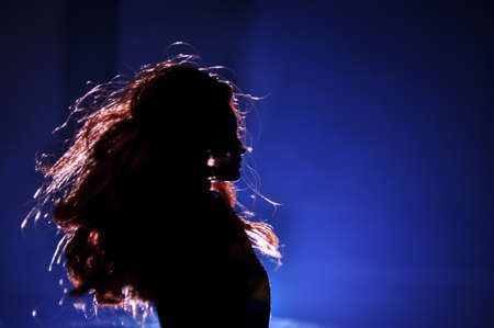Silhouette of a female face on a light background. SIlhouette of a lonely doll with long hair at night blue lights on foggy background. Selective focus