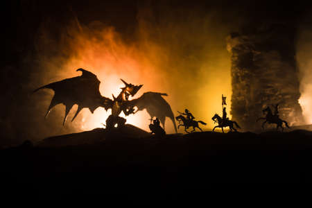 Fantasy battle scene with dragons attacking a medieval castle at night. Battle between dragon and heroic soldiers. Creative table decoration. Selective focus Stock Photo