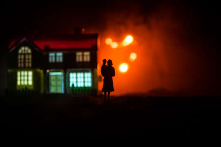 Silhouette of woman with child walking at cemetery at night. Horror Halloween concept. Artwork table decoration with light and smoke. Selective focus Stock Photo