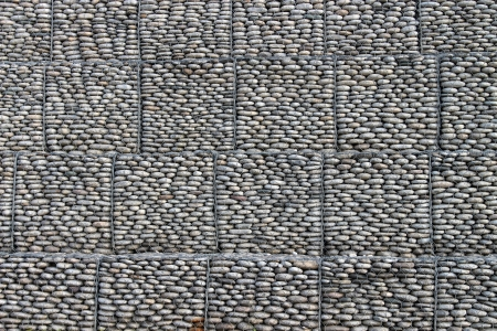 gabion: Wall of pebbles and stones in the iron grid Stock Photo