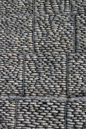 Wall of pebbles and stones in the iron grid photo