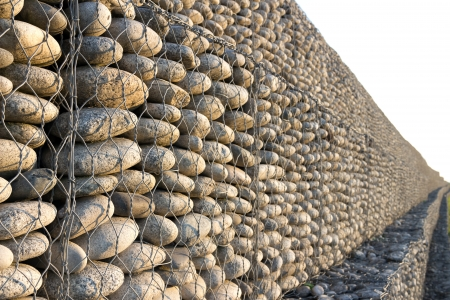 solid wire: Wall of pebbles and stones in the iron grid Stock Photo