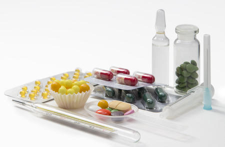 syringe, thermometer, tablets and capsules in blisters on white background photo