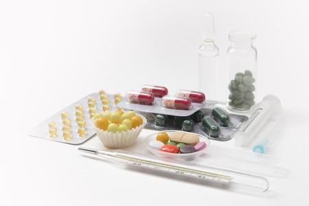 pilule: jeringas, term�metro, tabletas y c�psulas en ampollas en el fondo blanco