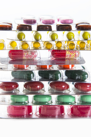 color of medicines in the blister - vitamins, tablets, capsules on the white background folded into a stack photo