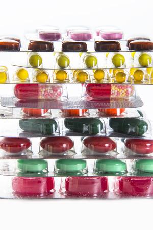 pilule: el color de los medicamentos en el bl�ster - vitaminas, tabletas, c�psulas sobre el fondo blanco doblado en una pila
