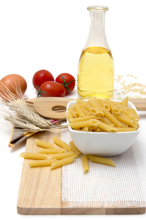 Italian pasta, macaroni quills with cherry tomatoes and olive oil in a glass bottle on a wooden board, white background photo