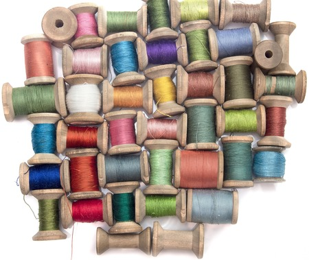 cotton thread: thread for sewing on wooden spools on a white background, handcraft, top view Stock Photo
