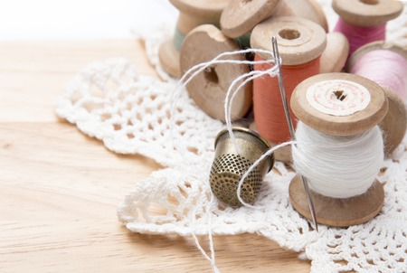 sewing cotton: cotton thread for sewing, wound on a wooden spool, white lace and a metal thimble, vintage on wooden background