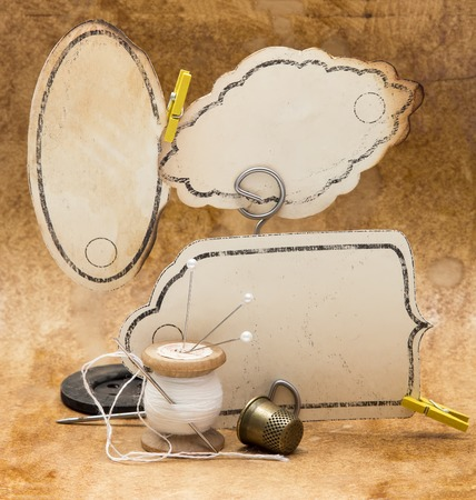 blank button: vintage frame and old tools for sewing, spool of thread, a thimble and needle, on a beige background, retro style Stock Photo