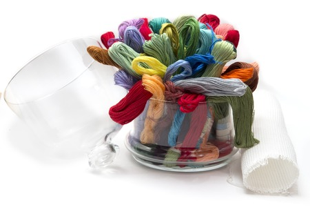 arts and crafts: set of colored threads for embroidery, folded in a glass vase, on the white background fabric and lace for sewing, arts, crafts, hobby Stock Photo