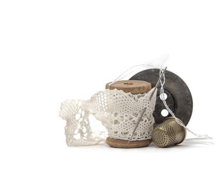 hilo rojo: carrete de madera vintage para hilo enrollado con encaje blanco para coser, aguja, botón negro de madera y un dedal de metal sobre fondo blanco, accesorios retro