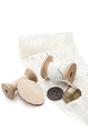 needle lace: thread for sewing on wooden spools with needle, empty spool of thread, buttons, metal thimble, and a piece of lace on a white background, retro style