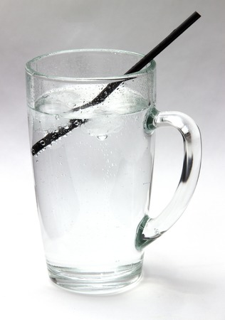 very cold: Drinking water. Daily drink a glass of very cold water, life giving water. Crystal clear water with ice in a transparent glass on a white background. Stock Photo
