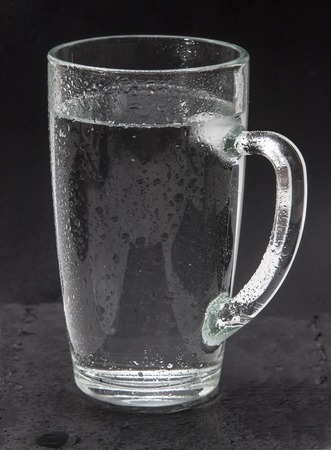 misted: Misted glass of cold water, water the source of life. A refreshing Cup mineral or soda water, tonic with hissing bubbles. Isolated on a black background. Drinking water.