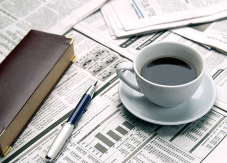 exceeds: Cup of coffee on the newspaper Stock Photo