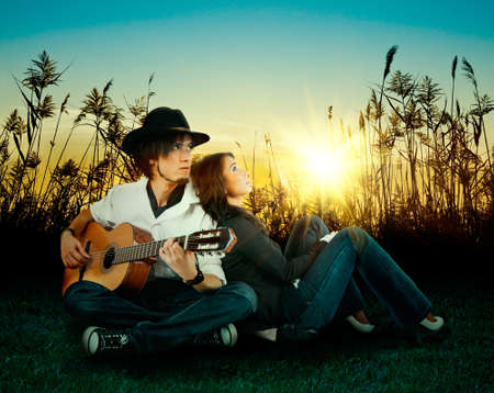 Love story  A young man playing guitar for his girl  photo