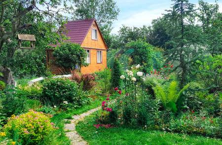Zomer houten huis op de achtergrond van groene tuin, landschap.