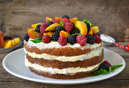 desnudo: Torta desnuda con crema, adornado con frambuesas, moras, melocotones Foto de archivo