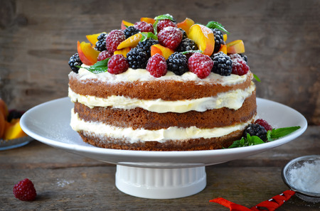 Naked cake with cream, decorated with raspberries, blackberries, peaches