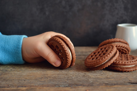 niños desayunando: galletas de chocolate en las manos de un niño