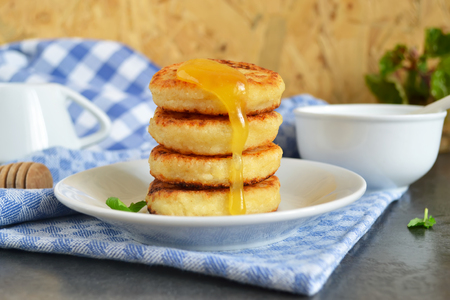 tast: Cheesecakes of cottage cheese with honey for breakfast Stock Photo