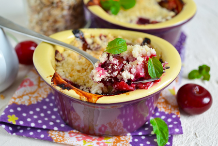 Cherry crumble with porridge on a concrete background