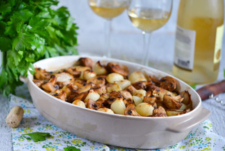bagre: Baked fish with mushrooms, potatoes and onions with a glass of white wine on a concrete background