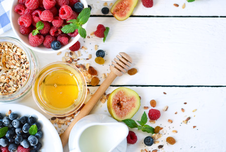 good food: Good morning - granola with honey, berries and fruits. White wooden food background, top view