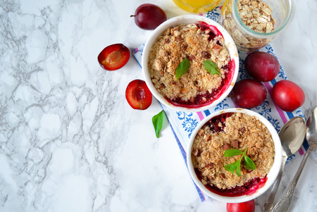 Oat crumble with plums, spices and honey on a light background 스톡 콘텐츠