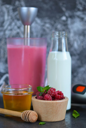 blender: Berry smoothie for breakfast with honey and raspberry on a black background.