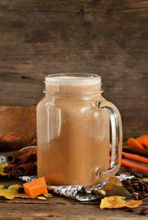 Hot latte with pumpkin, cinnamon and almonds on wooden background