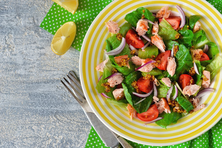 Frisse salade met gerookte zalm, tomaten, uien en saus op een concrete achtergrond