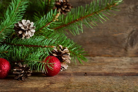 pinecones: Happy New Year - a holiday background with fir, balls, cones on the wooden background Stock Photo
