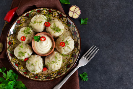Khinkali with meat and spices with spicy cream sauce and garlic on a black background. Top view.
