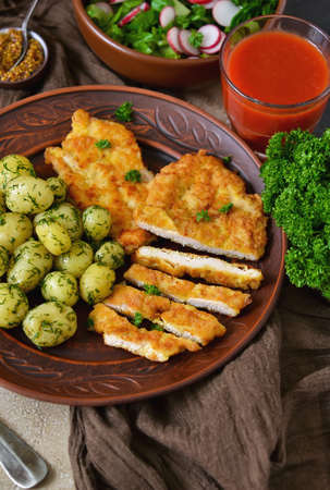 Schnitzel with potatoes and salad for lunch on a concrete background  Stock Photo