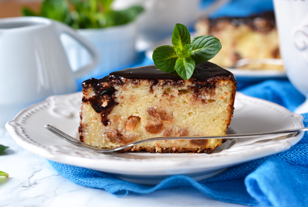Homemade cottage cheese casserole with raisins and chocolate on a marble background
