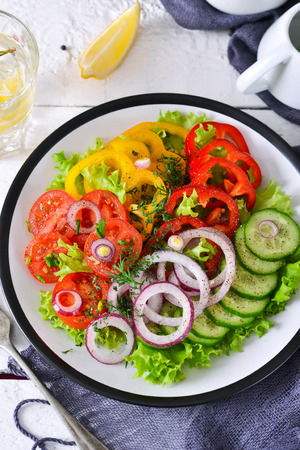 Vegetable mix salad with avocado and olive oil sauce on a white, wooden background.