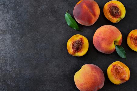 Fresh, juicy peaches on a black stone background. Organic food. Stock Photo
