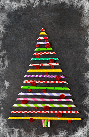 Decorative christmas spruce made of colored pipes on a black background. New Year card.Abstraction.