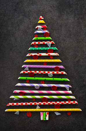 Decorative christmas spruce made of colored pipes on a black background. New Year card.Abstraction. Stock fotó