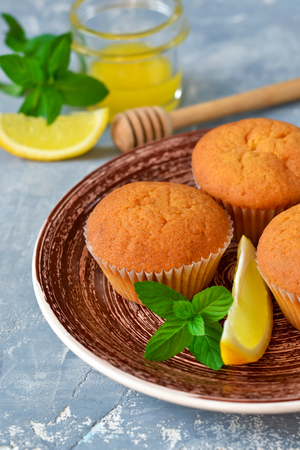Homemade, lemon muffins with honey and mint on a concrete background