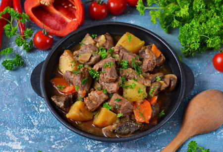 Meat goulash with vegetables, potatoes and mushrooms on concrete, grunge background