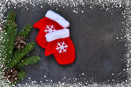 Zwarte Nieuwjaarachtergrond met decoratie van sparren en vuisthandschoenen. Gelukkig nieuwjaar en vrolijk kerstfeest Stockfoto